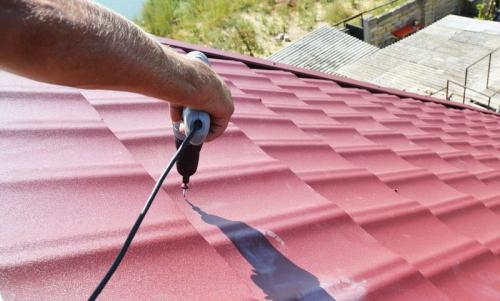 Roofing contractor installing metal roof tile for roof repair after hurricane damage.