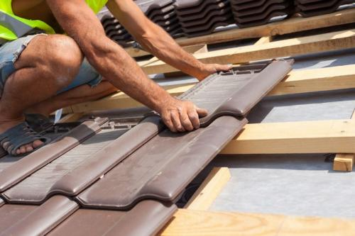 Hands of roofer laying tile on the roof.